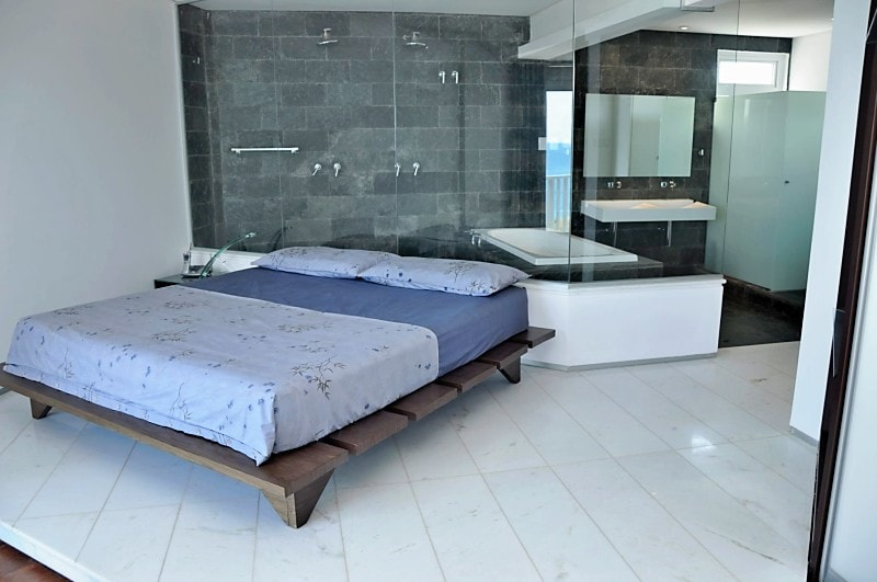 Master-suite, king-size platform bed, black slate bathroom, dual shower, soaking tub, dual sink, opaque glass-enclosed toilet