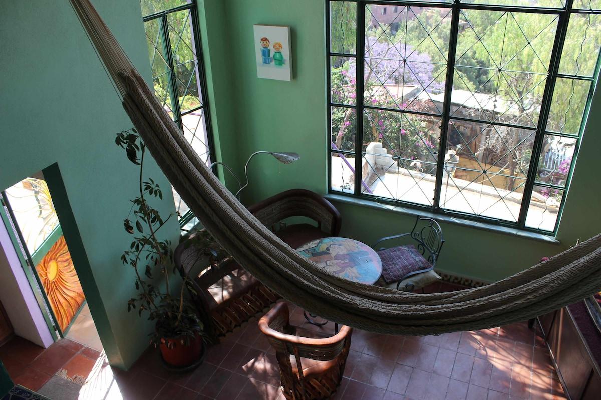 A hammock swings between the bedroom and living room