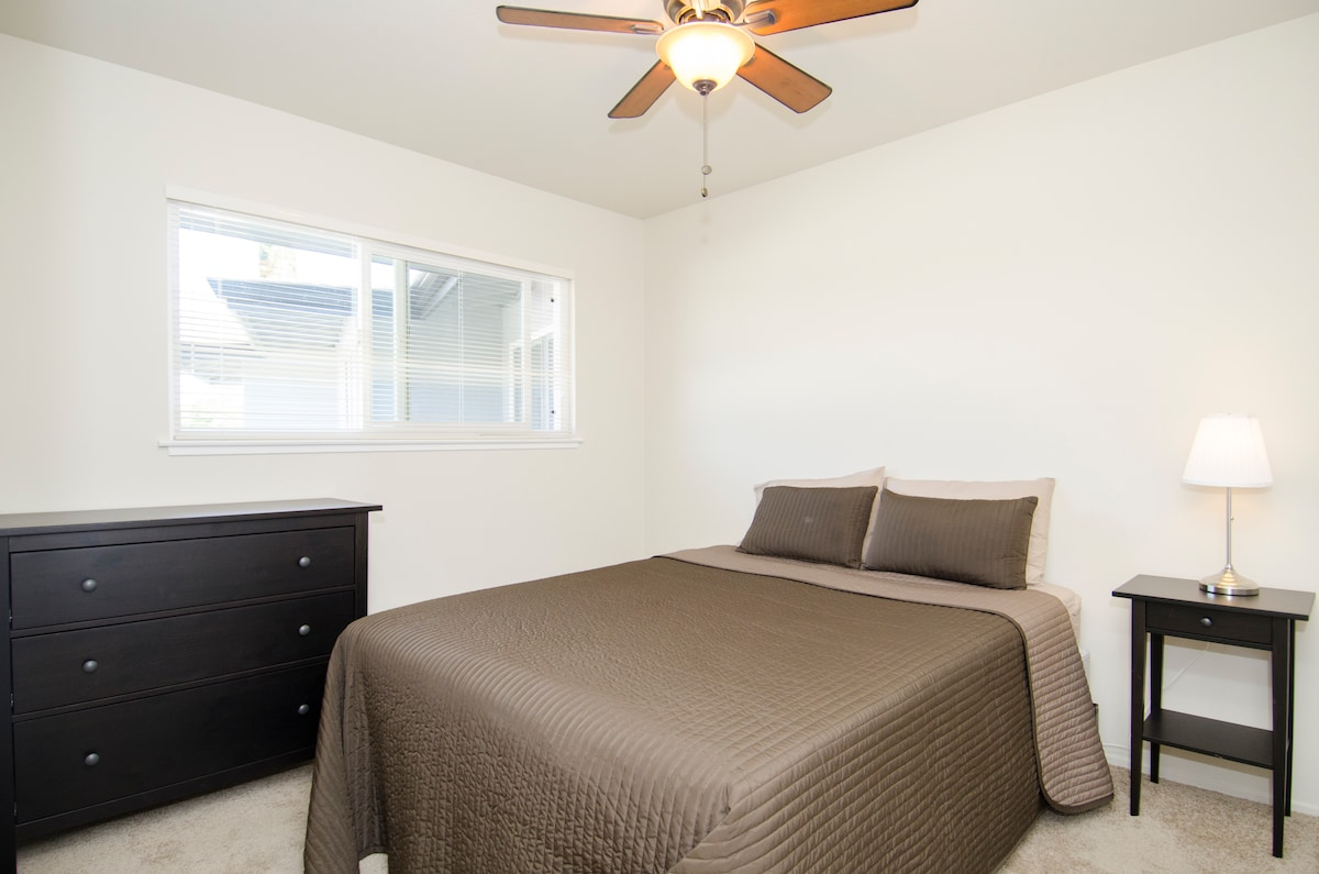 Bedroom showing new Queen bed with full linen sets, dresser, night stand, lamp, double-paned windows, and overhead fan