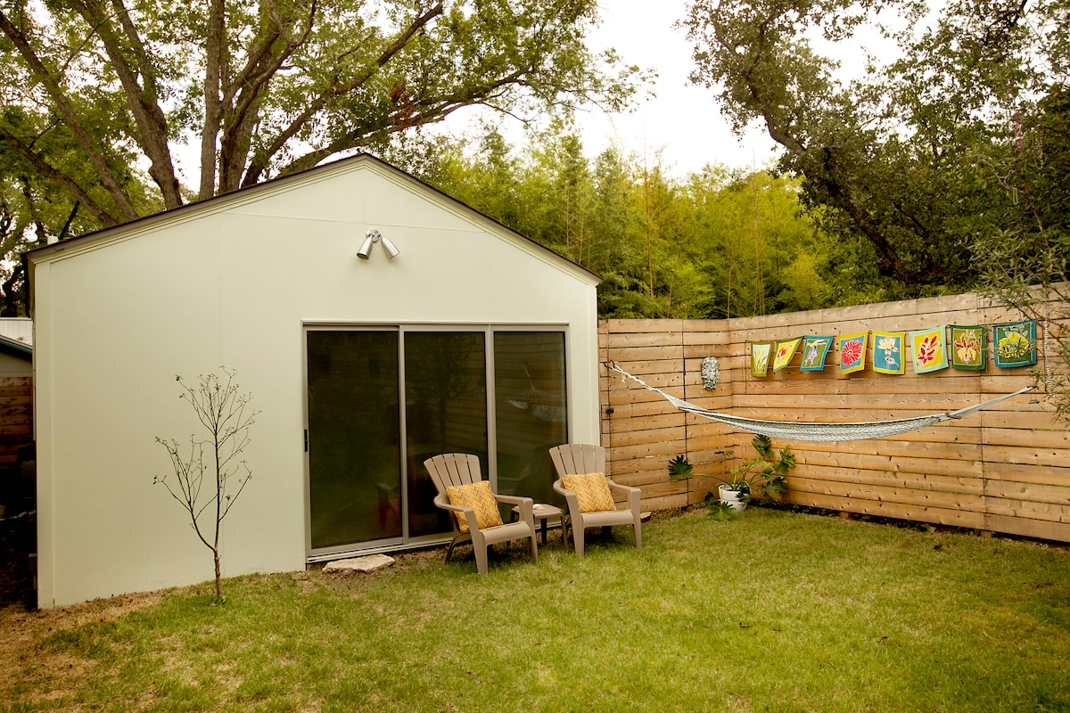 The outside of the studio rental, with sitting area in the backyard.
