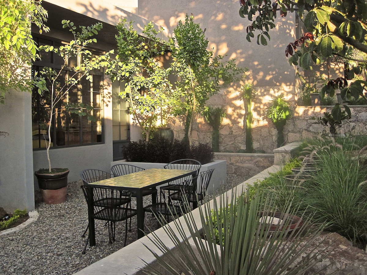Garden setting with outdoor seating, great for coffee or reading.
