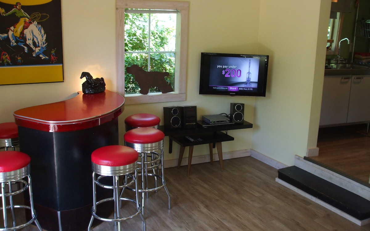 Half of the living room with HD TV, Stereo with Ipod player and bar.