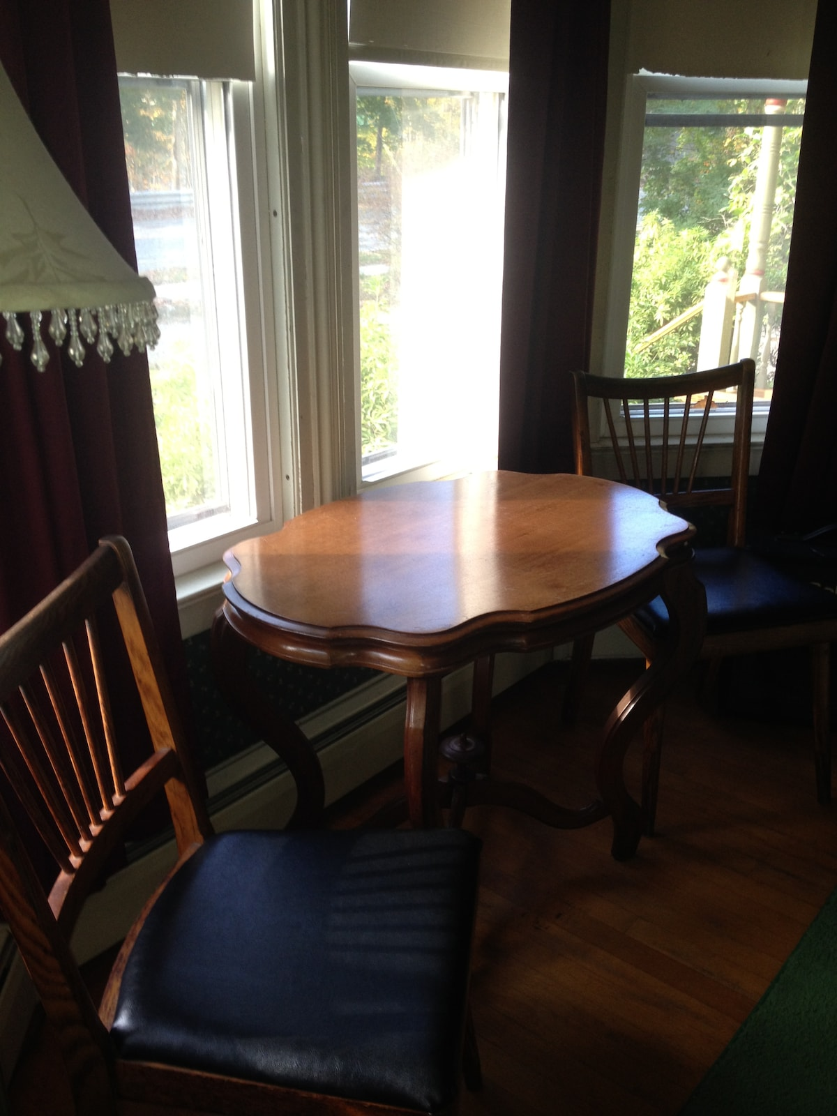 Small table and two chairs in the bay window in your room