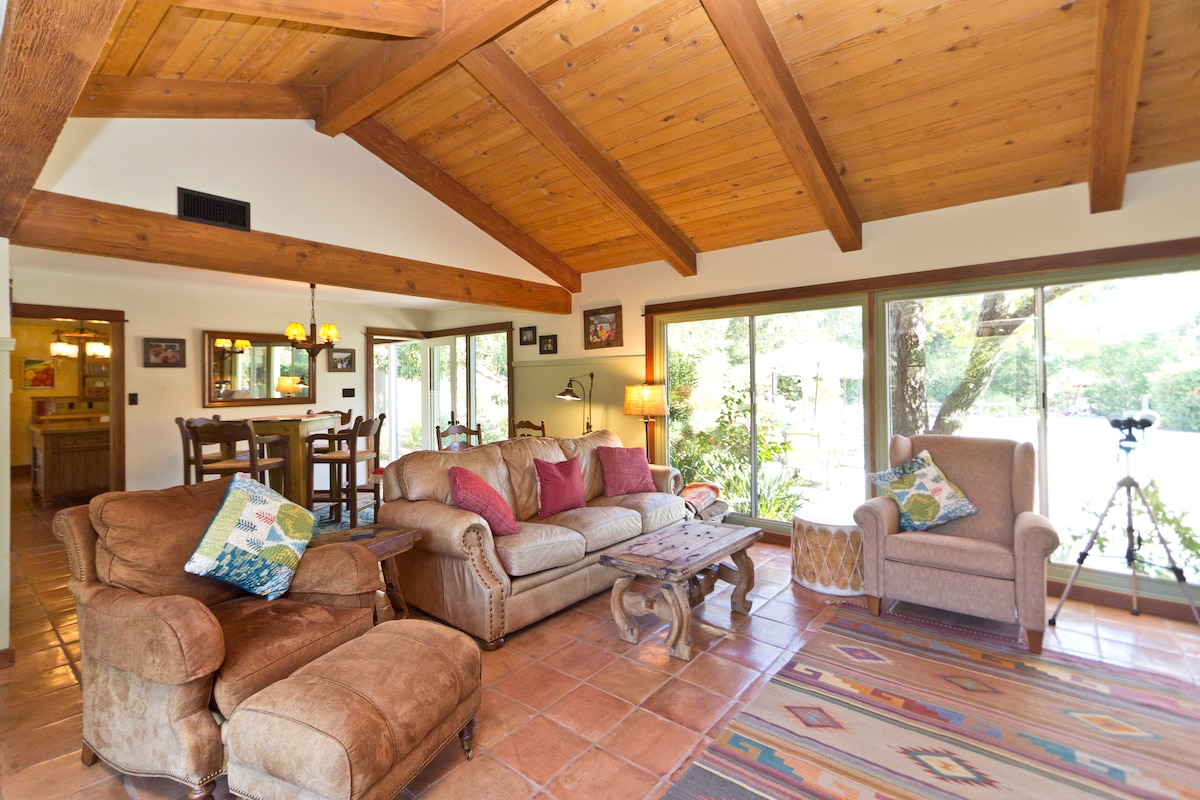 Rich exposed-wood vaulted-ceiling and fireplace make the living room extremely cosy
