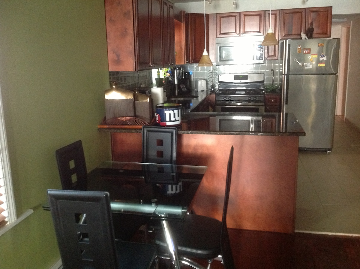Stainless steel and granite kitchen with dining table.