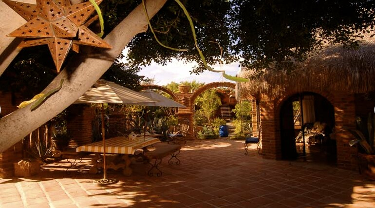 beautiful large courtyard claimed by magic laurel tree, buganvilias and brick arches, enter bedroom palapa at right