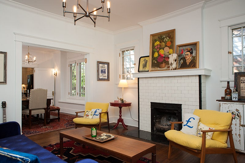 Light and airy living room with seating area, vintage bar, original fireplace newly restored crown molding, 1960s mid-century chairs