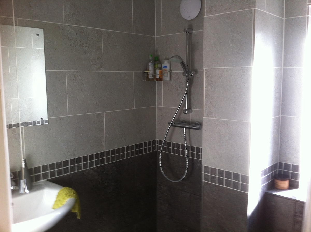 En suite wet room with heated floor and towel rail.