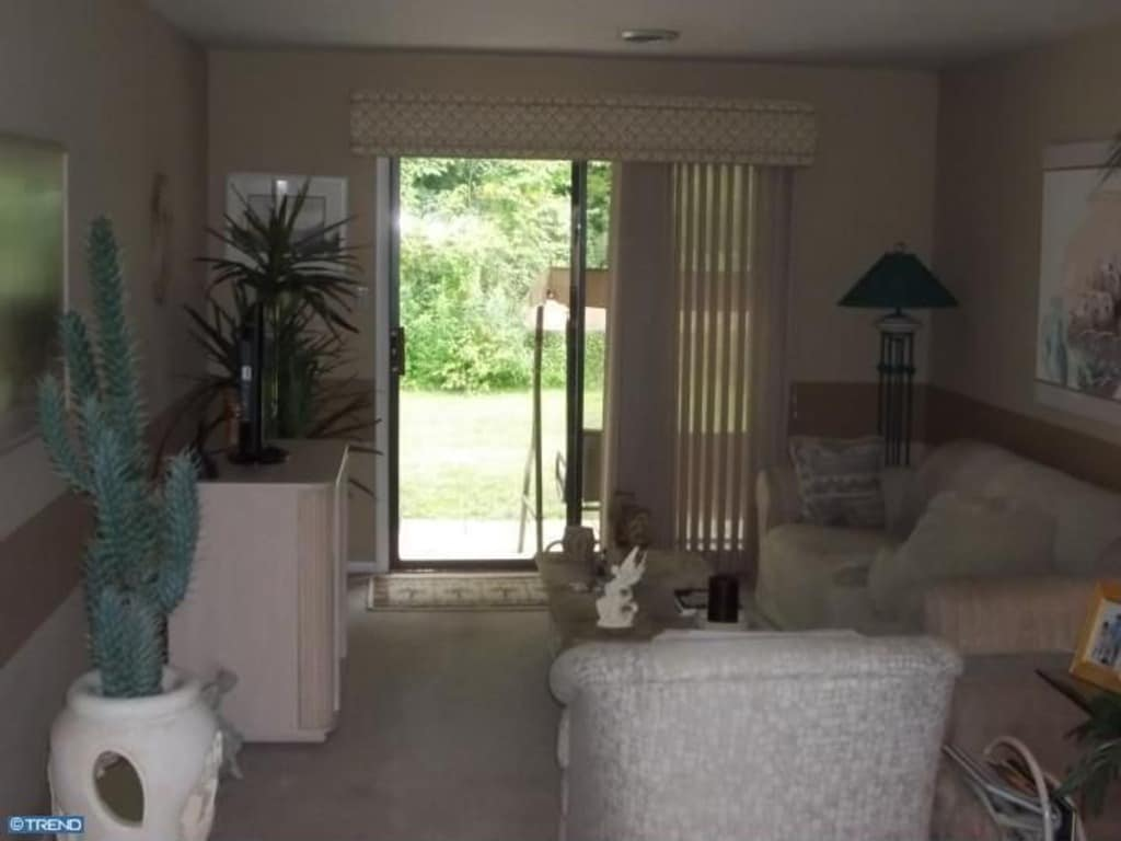 Living Room area; patio looks out on lovely wooded area running the length of our building.