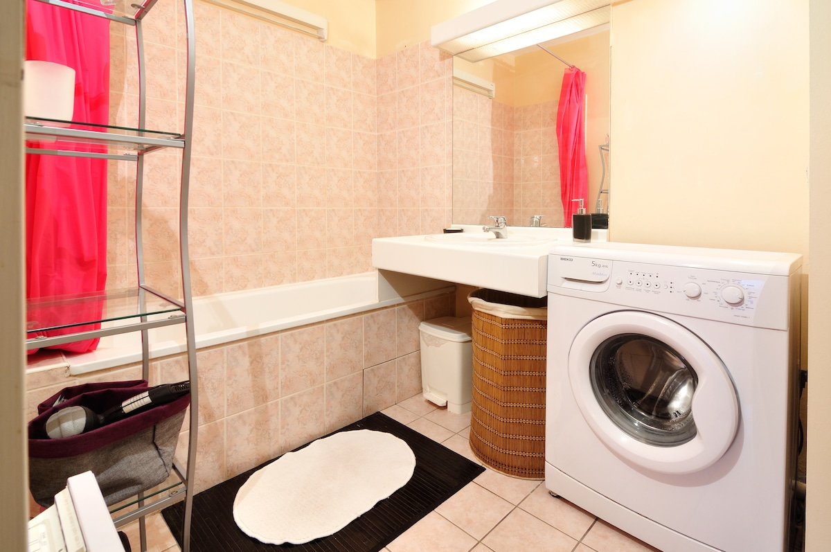 La salle de bains, avec baignoire et lave-linge. // The bathroom, with bathtub and a washing machine.