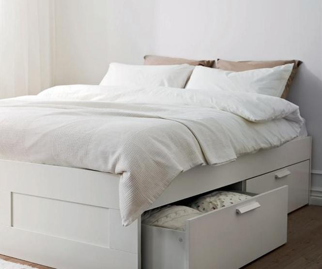 Queen size bed with many pillows and storages