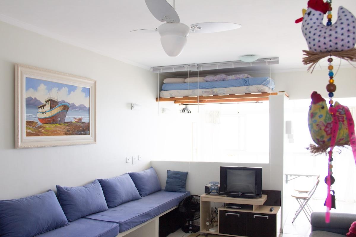 Sala ampla e arejada, com ventilador de teto.