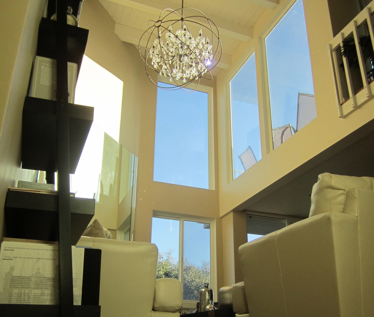 The main floor has a huge vaulted ceiling with large glass windows that allow lots of natural light to flow through the house