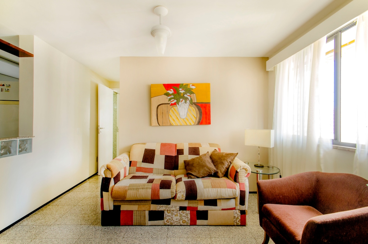 Sala com sofá cama e tv a cabo.