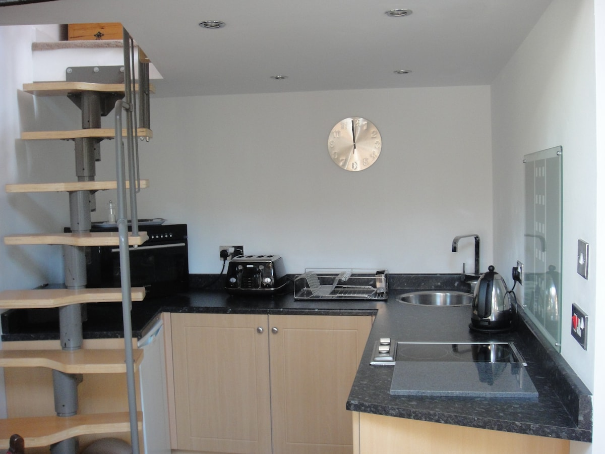 The well equipped kitchen area and steps to the mezzanine bedroom