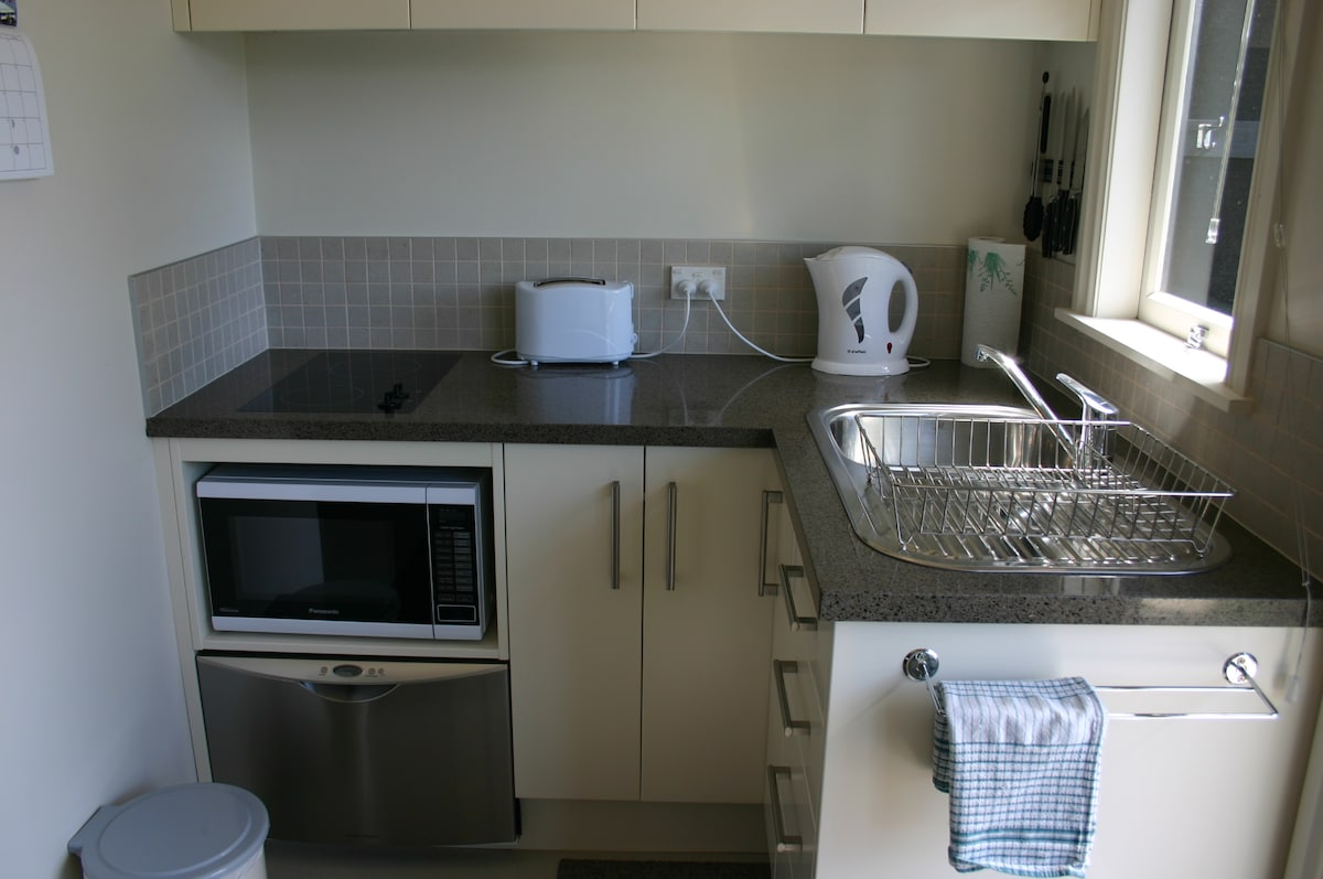 The kitchen  has a microwave and dishwasher and is modern, easy and new.