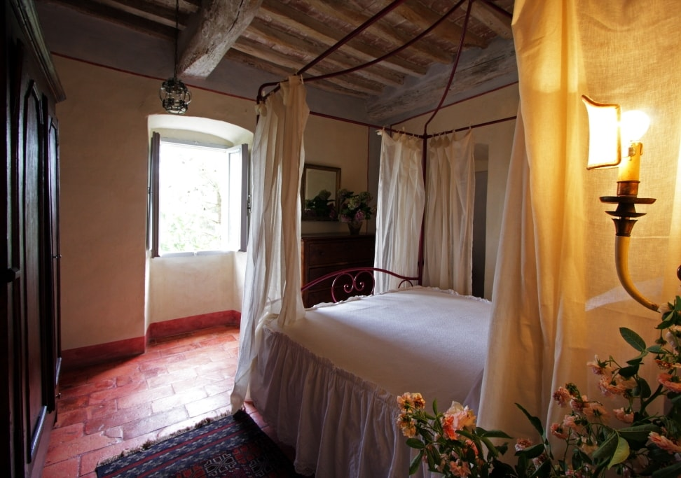 the master bedroom with its four poster bed and original ceiling and floor