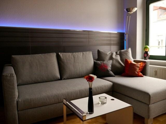 Gemütliches Ecksofa vor der Fliesenwand mit Delight-LED-Leiste (separat mit Fernbedienung zu schalten)