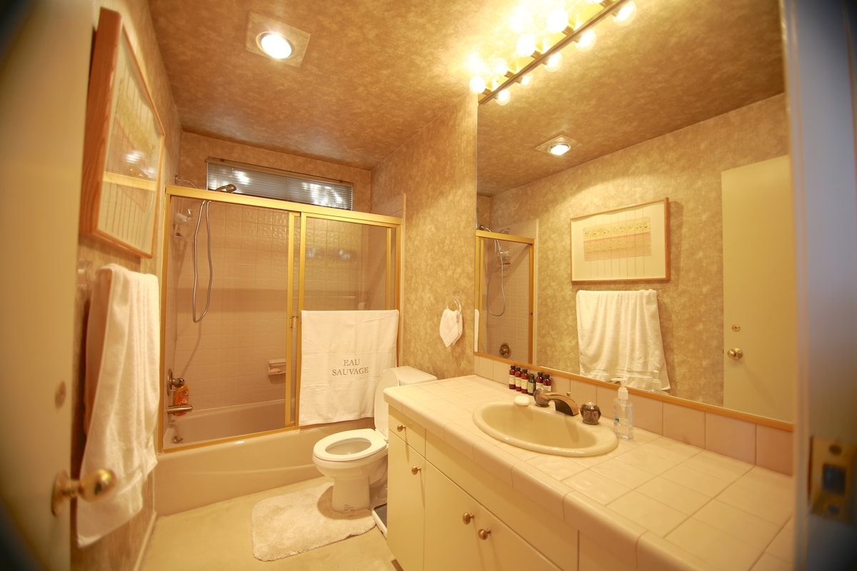 Private bathroom with air conditioning, large mirror and lighting.