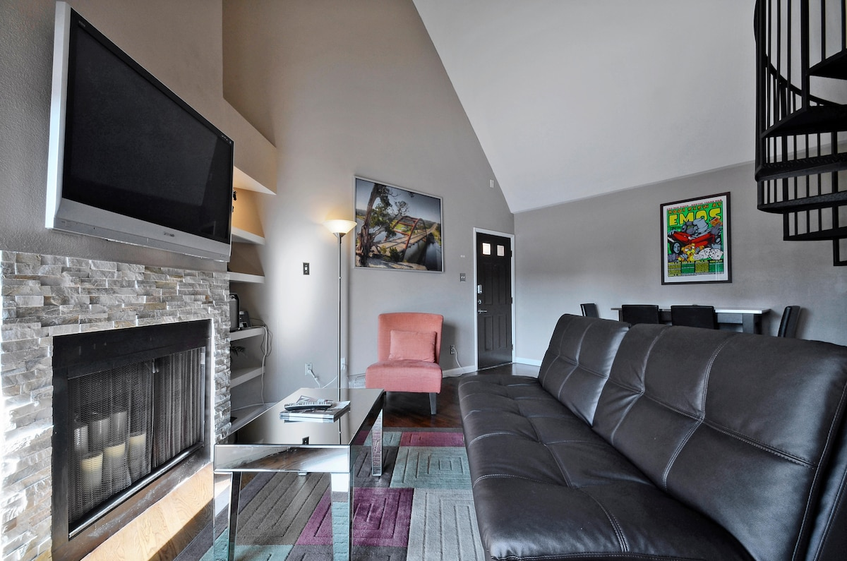 The common area has a wall mounted television and plenty of comfortable seating.