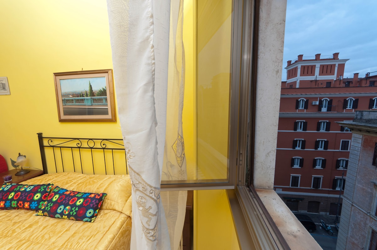 Yellow double bedroom, with queen size bed, and a wide window