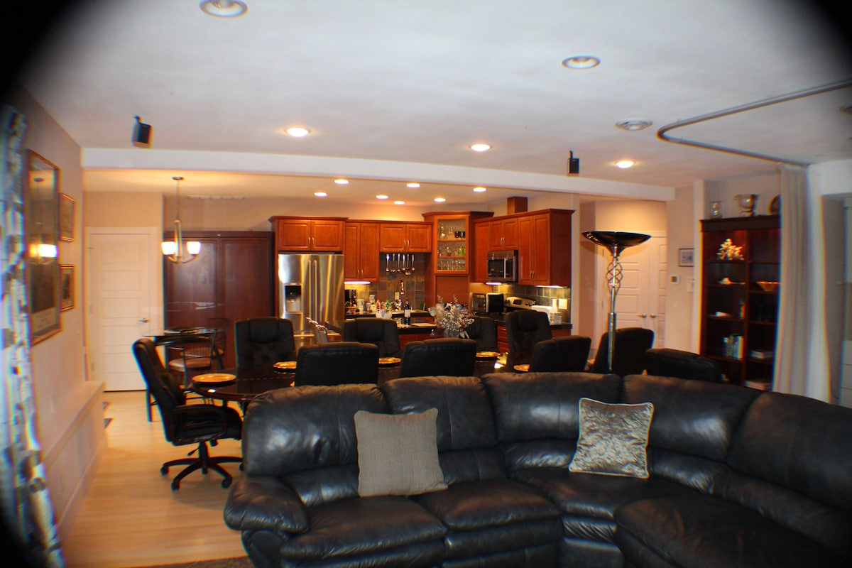 Living room leather sectional with recliners into dining room and large kitchen