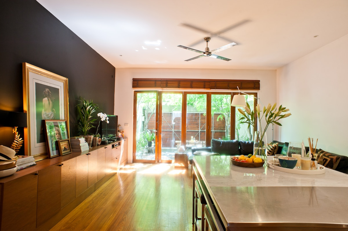 Open plan living and kitchen with marble and stainless steel bench