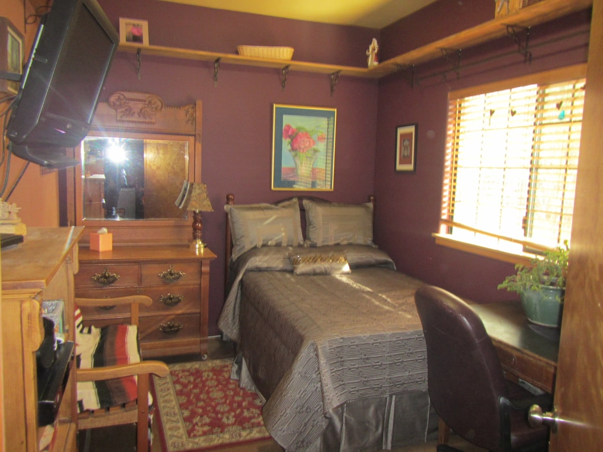 Comfortable bedroom with TV.and Wifi,closet,desk,and antique dresser. view  of bird feeder outside.