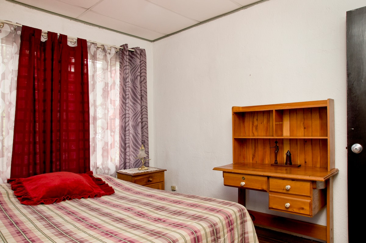 Clean and comfortable bedroom with a queen size bed and desk