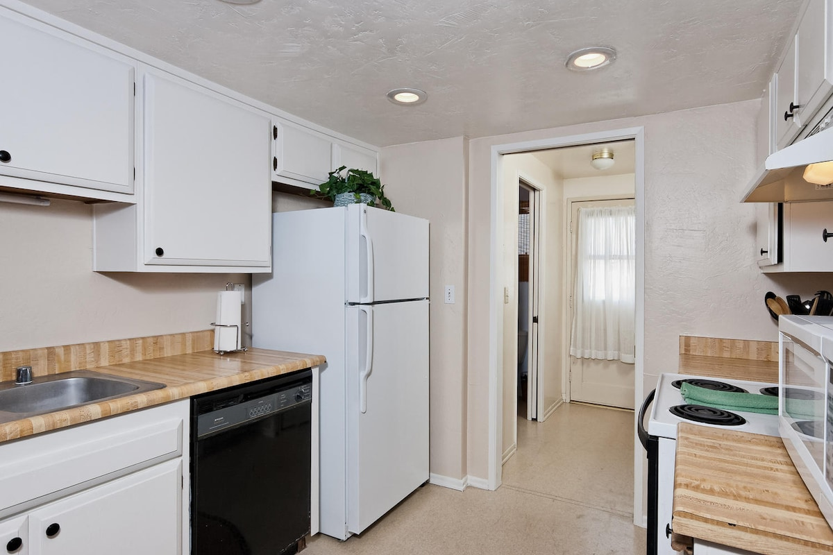 Plenty of storage, dishwasher, microwave, NEW gas range (picture does not show updated appliances) and new dishwasher- Laundry room, Half bathroom and door to outside area...