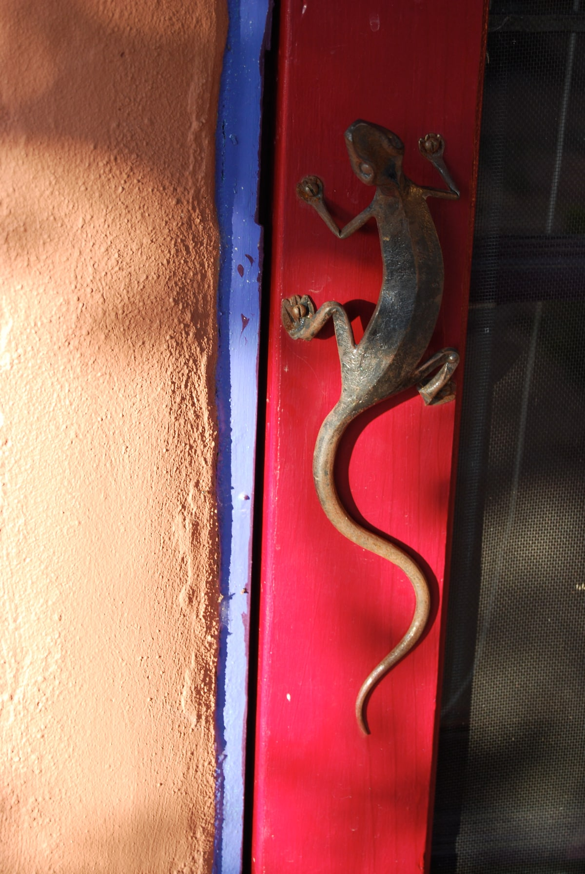 On the front screen door this hand forged lizard handle is a typical detail.