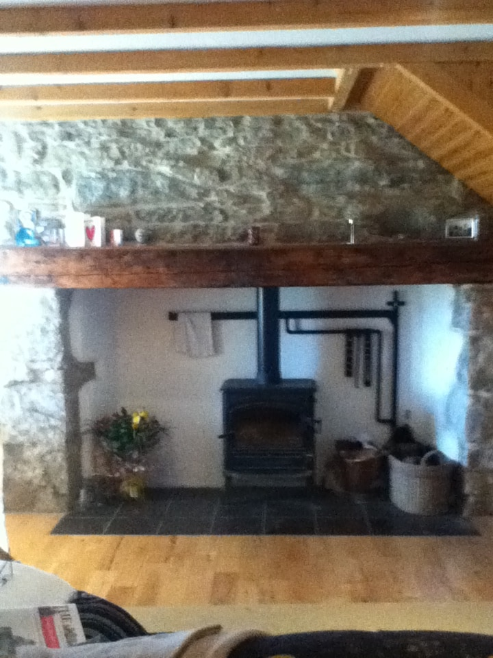 Large inglenook fireplace with stove.