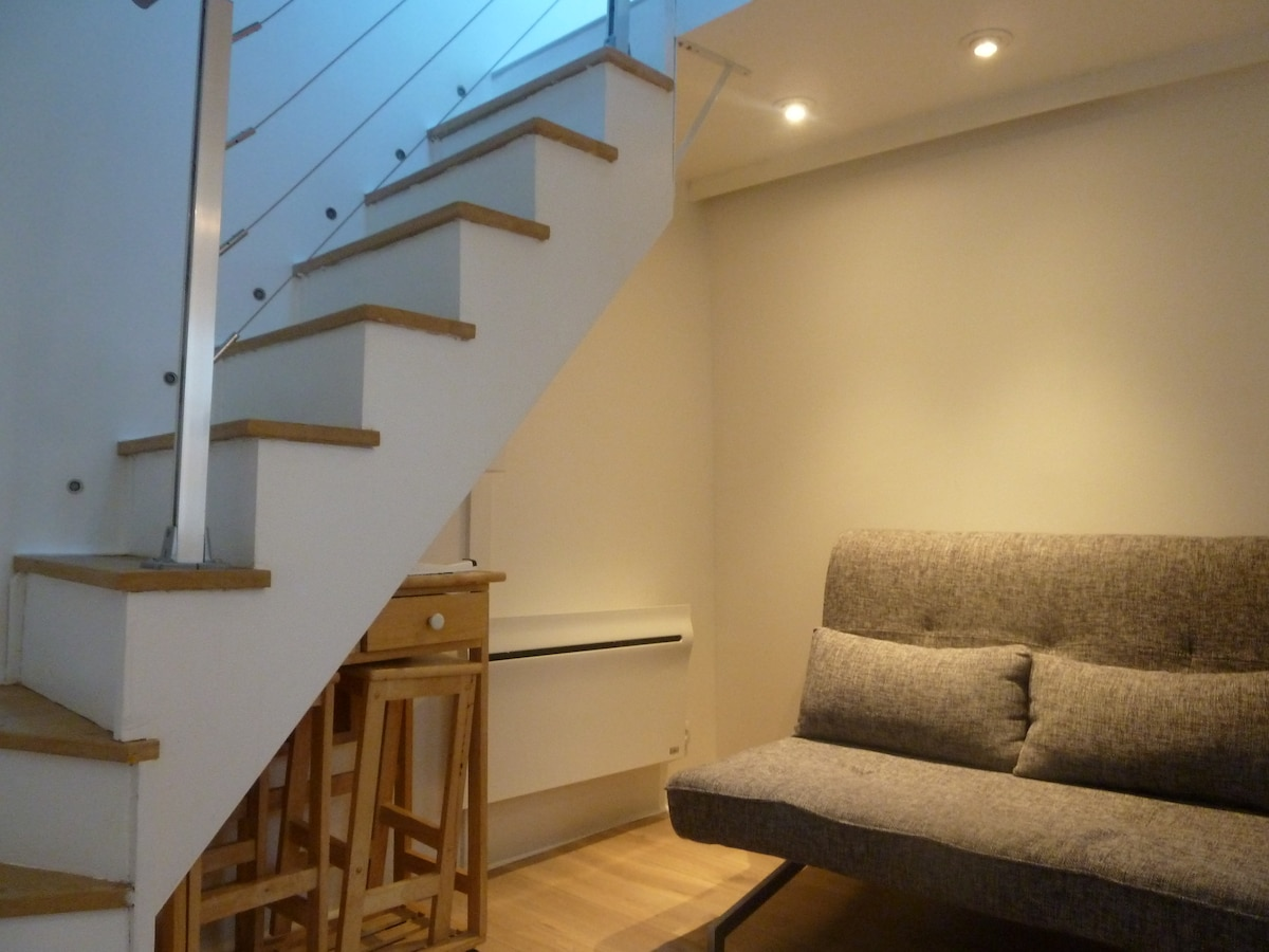 Sofa-bed in living room & stairs to bedroom