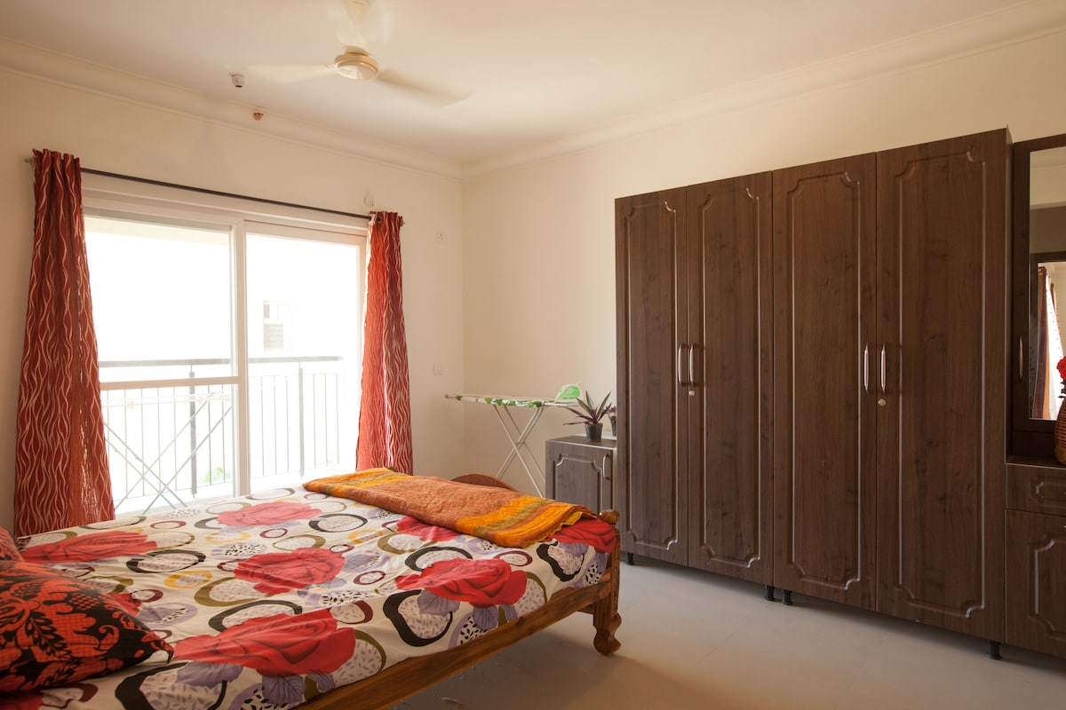 Sunny Master Bedroom with sit out balcony - attached luxurious bathroom, real teak double bed, comfortable mattress, 5 door dresser, iron box and stand, vacuum cleaner - hill view