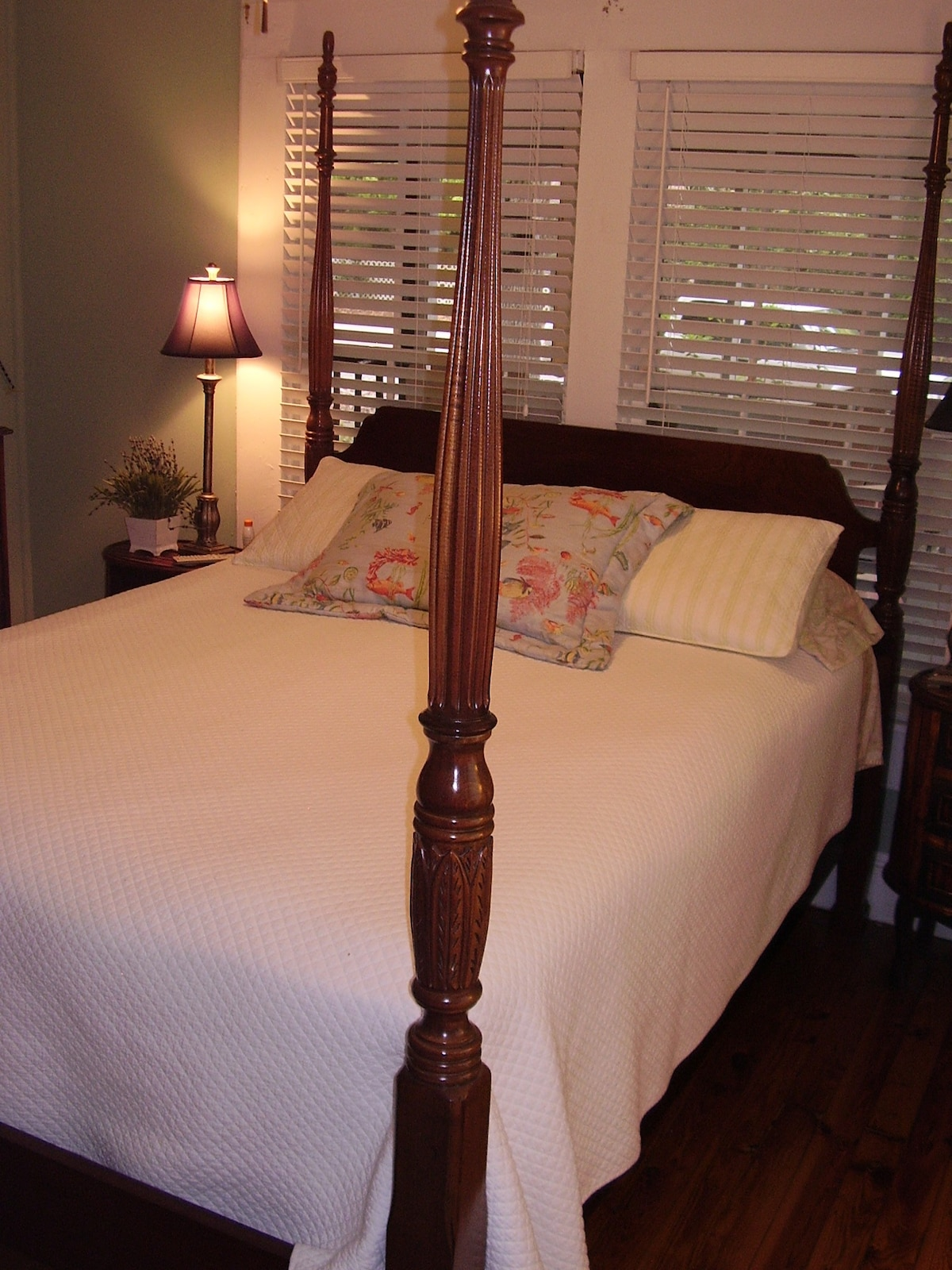 Tall-poster bed in the Master bedroom looks out to the front porch