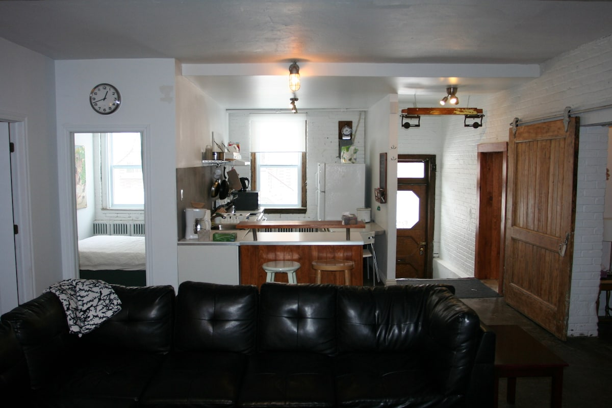 View of the kitchen, front door, and one of the bedrooms from the red sofa