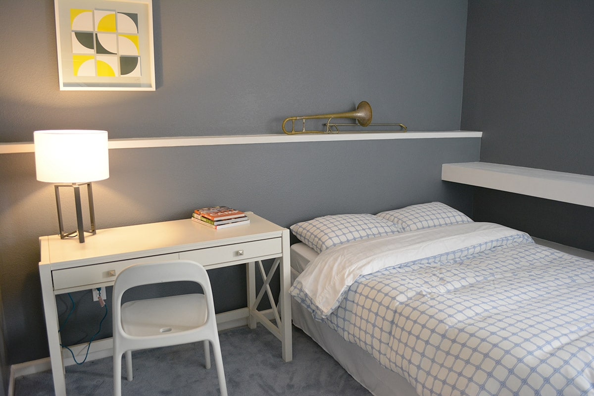Gray and white room. Full-size bed, desk, chair, window.