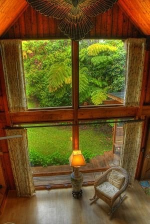 The large picture windows allow views of the forested surroundings.