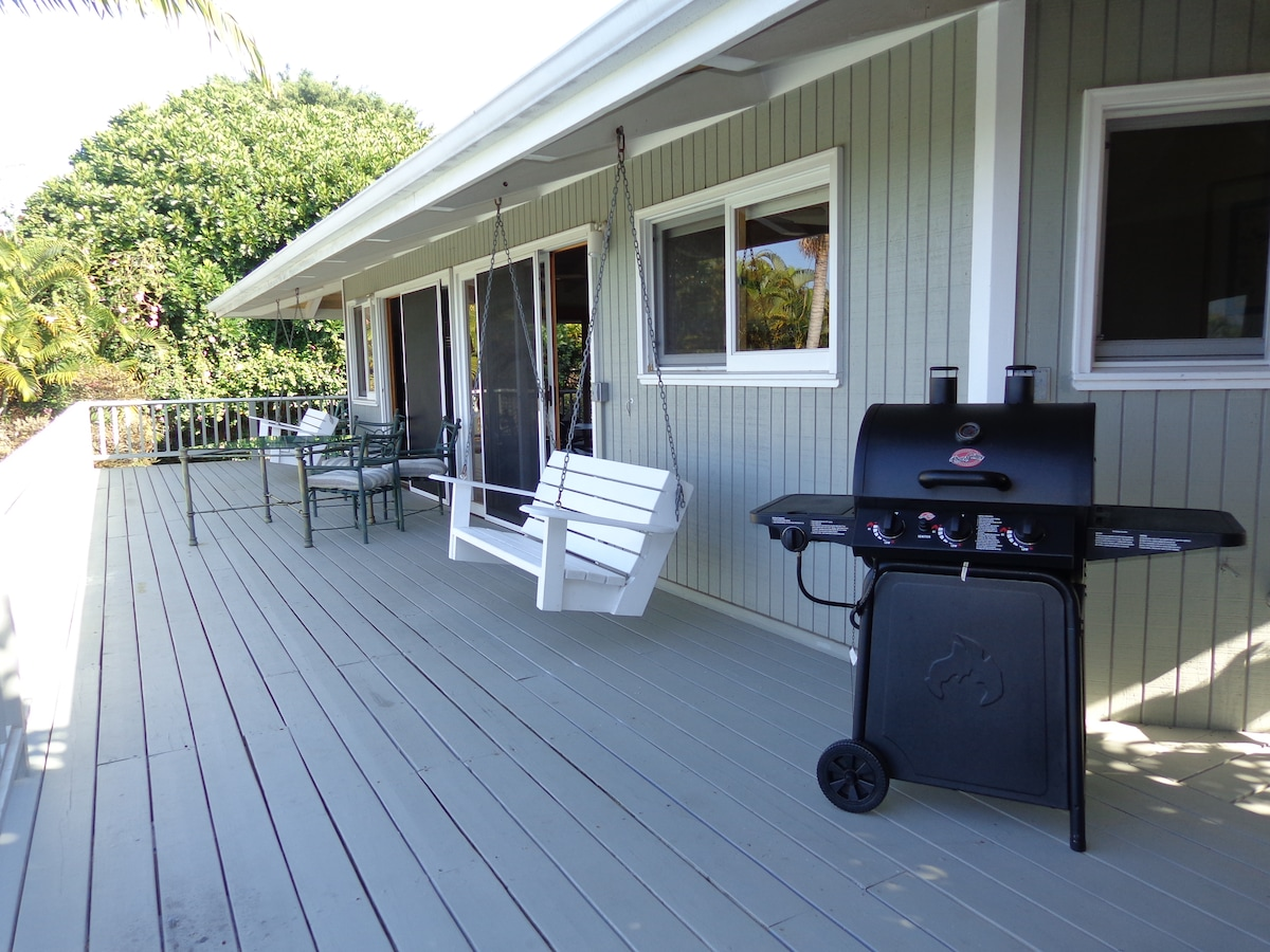 Wrap around lanai with porch swings, table and chairs and a BBQ.