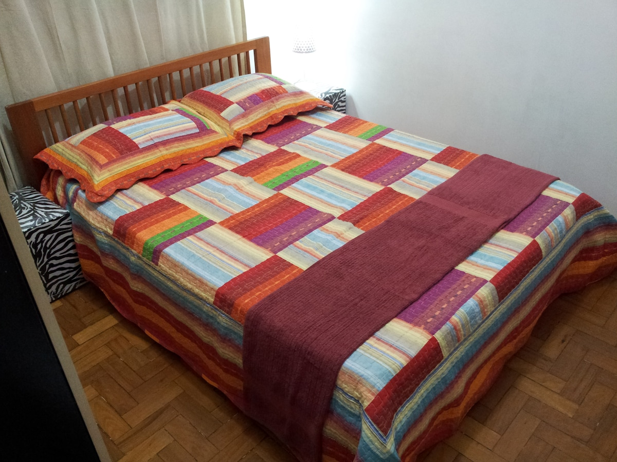 Bedroom with a double bed, 2 side puffs, air conditioner, and closet -