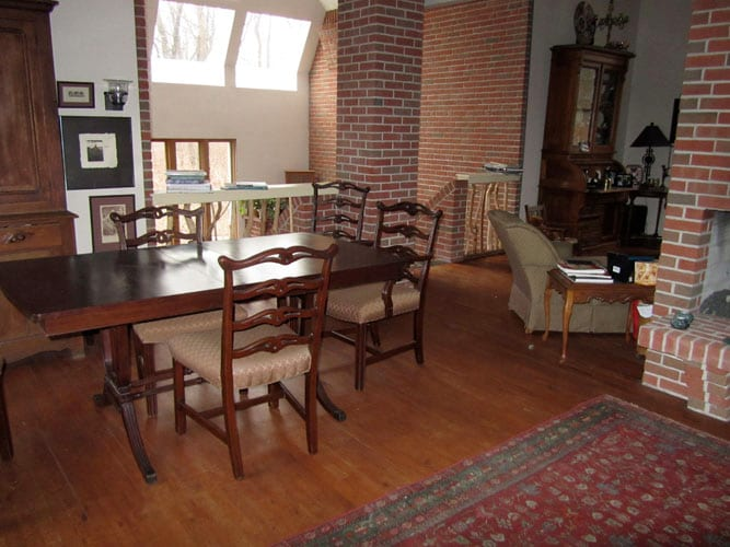 Dining room with original art, bare branch railings and antique oriental rugs.