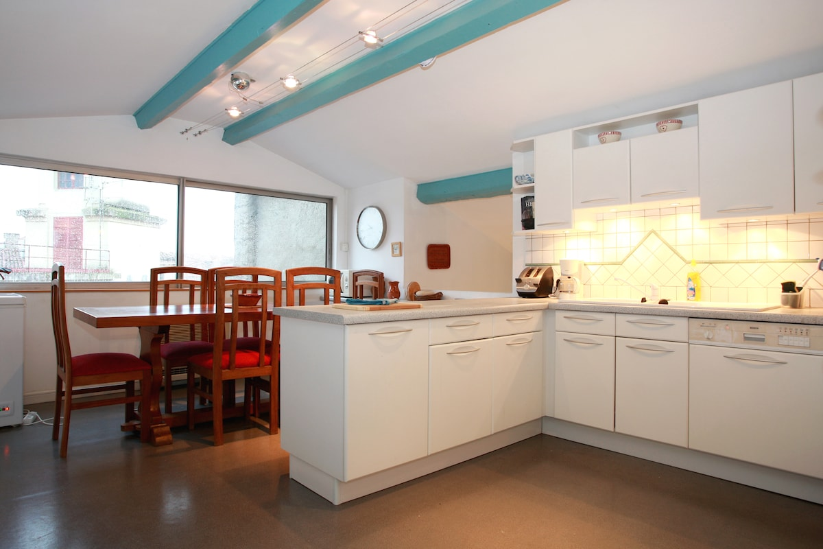 Well equipped light  kitchen with bar and large dining table