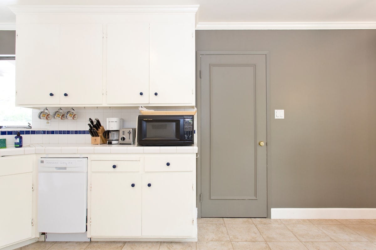 Dishwasher, microwave (and good quality knives!) to right of the sink. Double locked & insulated door connects to a studio apartment, which is a separate Airbnb unit.