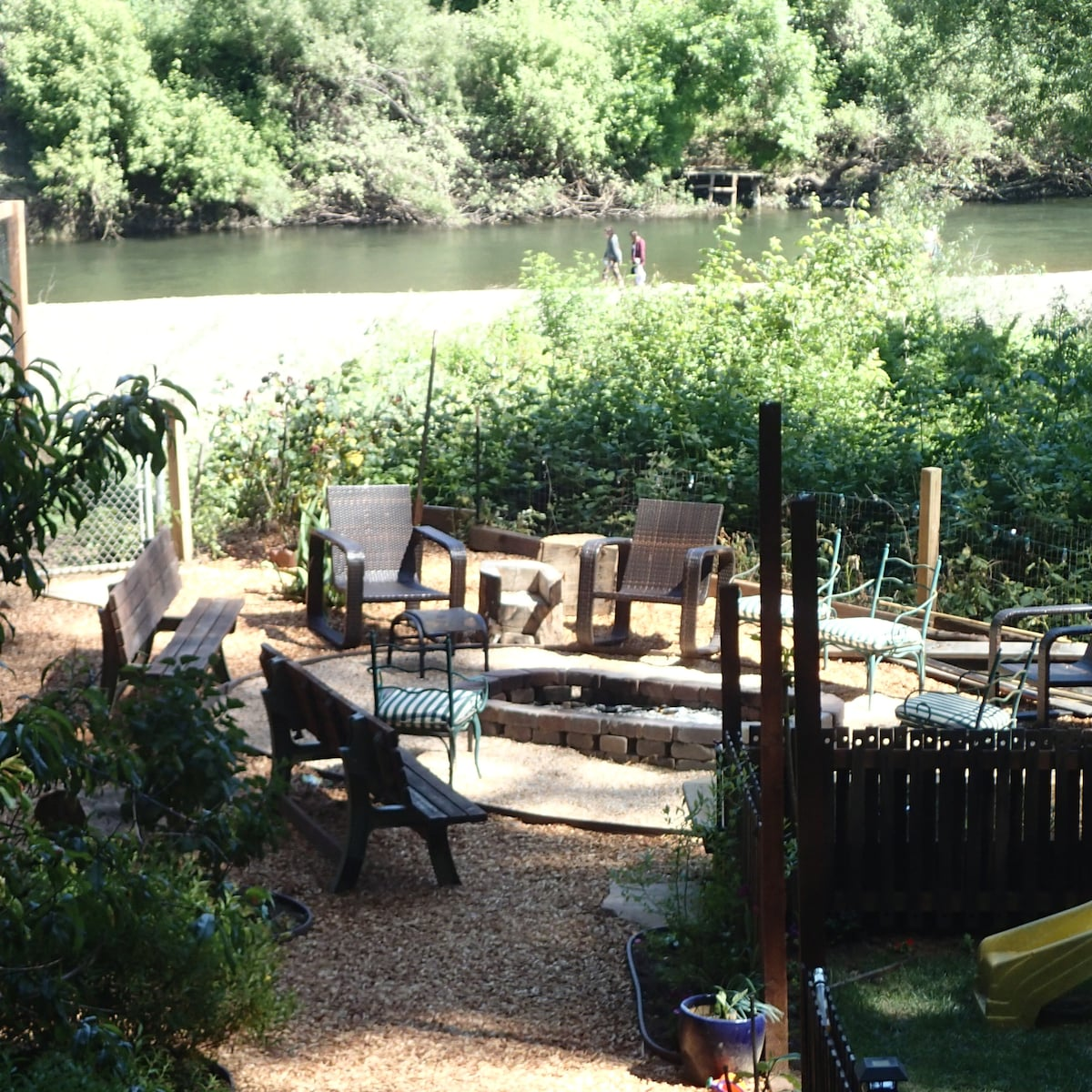 Large fenced yard, fire pit, play scape, veggie garden and river views