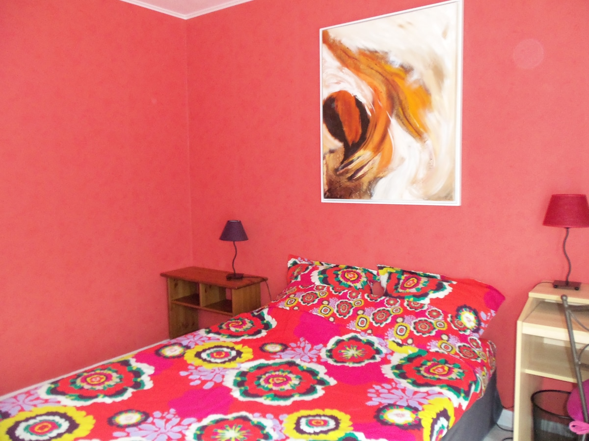 Un espace de rangement (chevet ou bureau) et une lampe de chaque côté du lit.