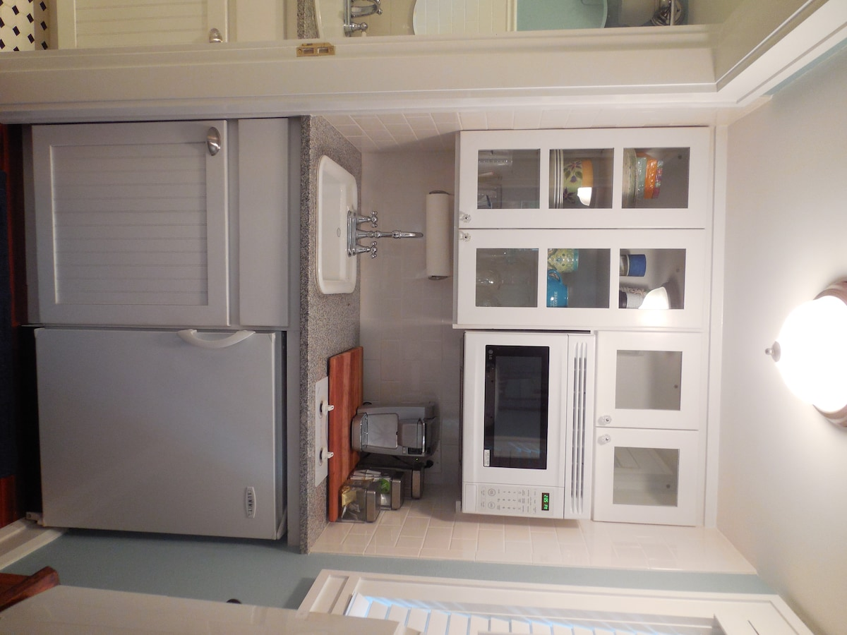 The first floor kitchenette with refrigerator, microwave, sink and coffee maker.
