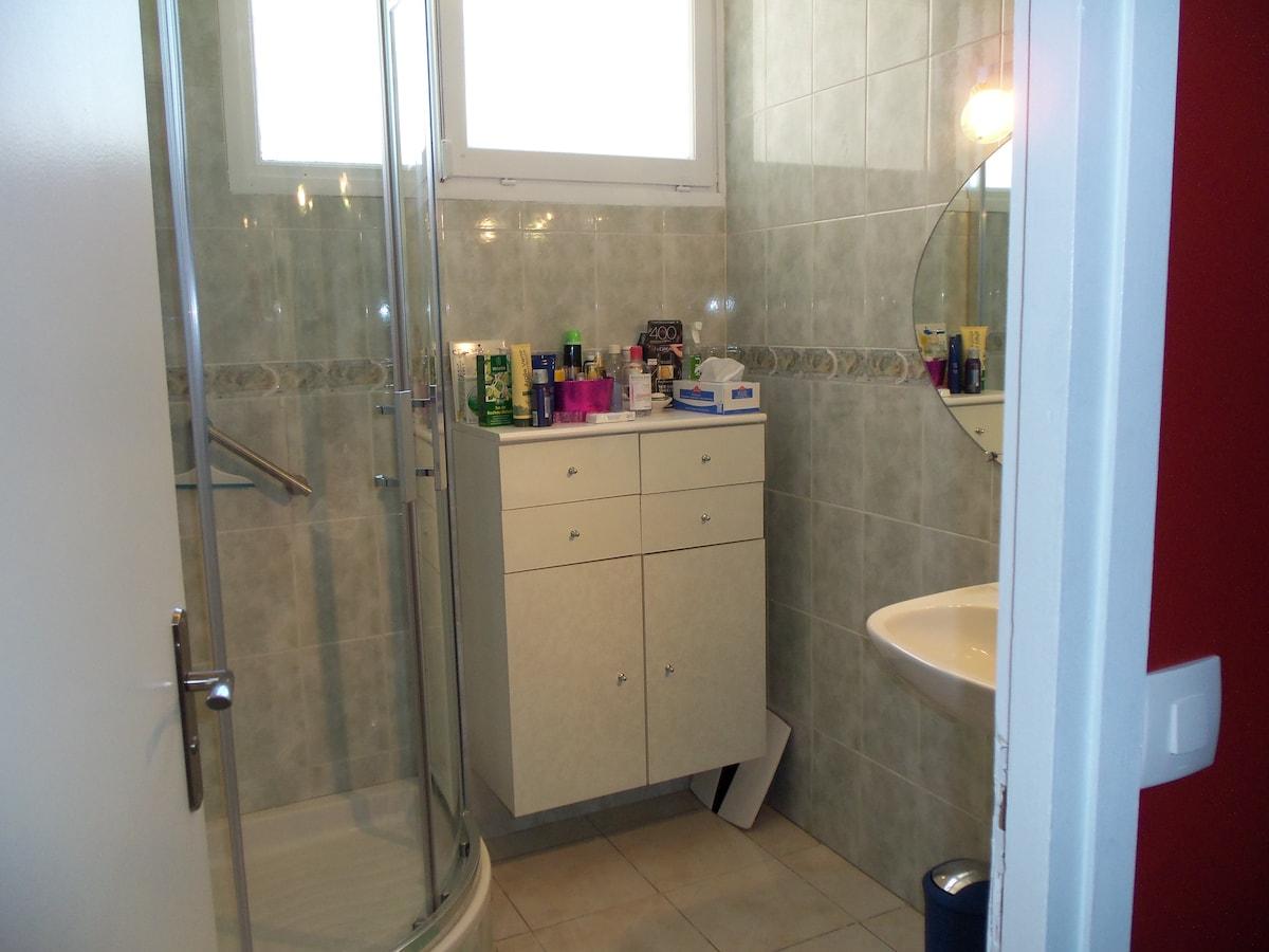 La salle de bain, lumineuse et bien aérée.