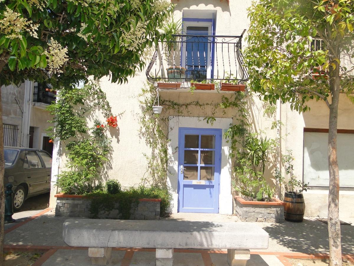 façade ensoleillée charmante petite maison donnant sur une jolie petite place