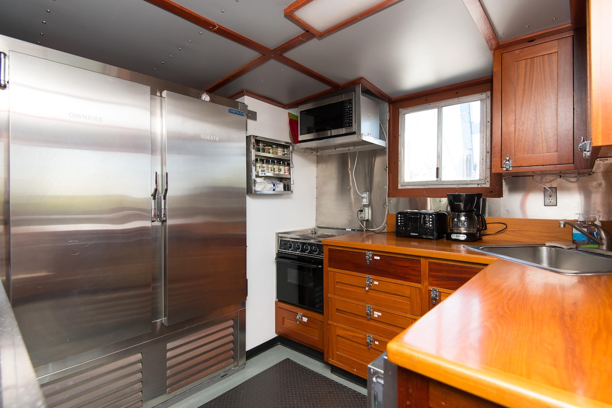 The galley, aft of the Salon, provides a ginormous commercial refrigerator, microwave, toaster, coffee maker, plenty of undercounter lighting and all your typical cooking utensils.