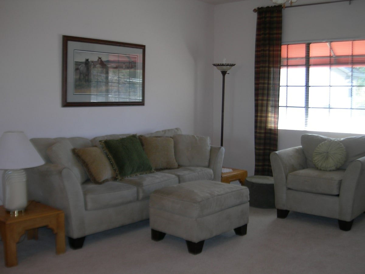 One of the living room couches and a chair & ottoman